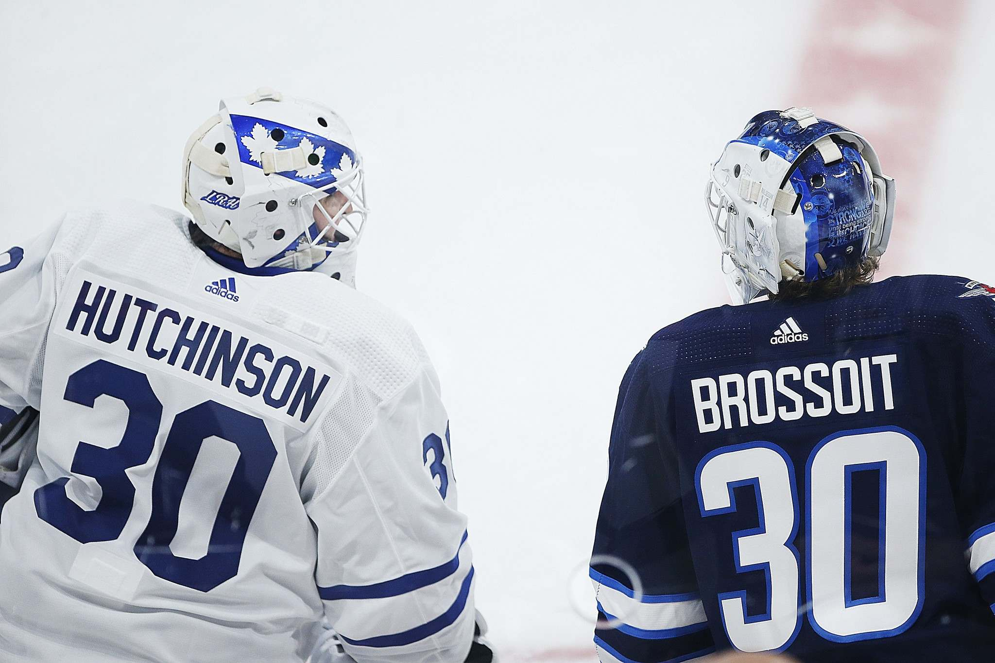 Hutchinson chats with Jets goaltender Laurent Brossoit during warm up Wednesday.