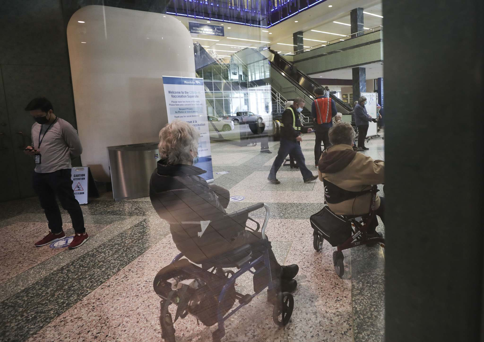 RUTH BONNEVILLE / WINNIPEG FREE PRESS People wait their turn in line as seen through the window of the main floor of the vaccination centre at The RBC Convention Centre Thursday. </p>