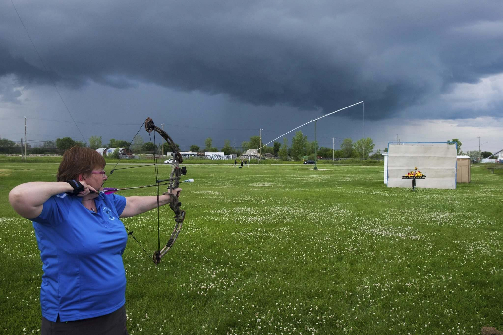 Denise Arcand of the St. Sebastianette Archery Club lines focuses on her target as storm clouds gather on the horizon.</p></p>