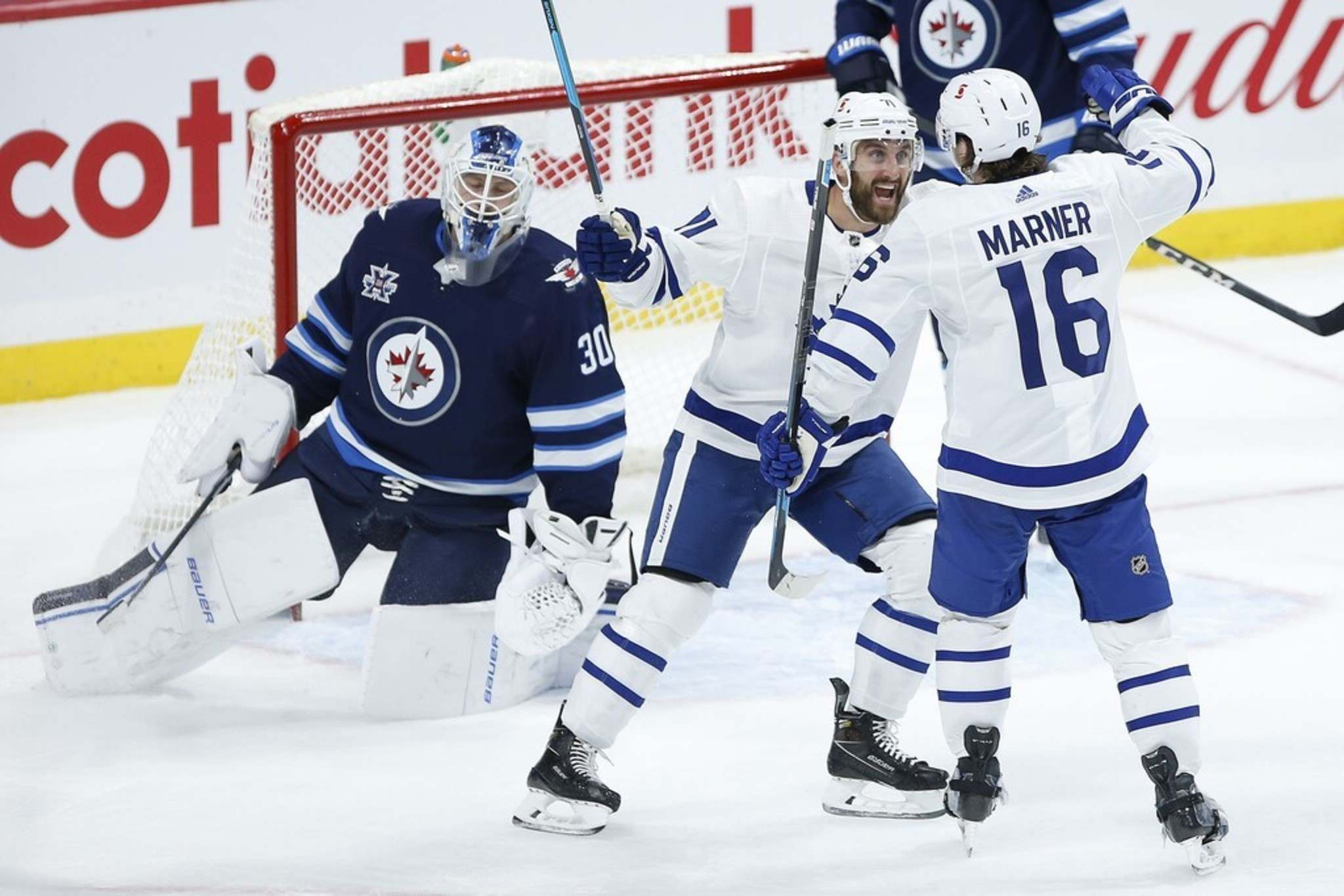 Toronto Maple Leafs' Nick Foligno, left, and Mitch Marner celebrate Marner's goal on Winnipeg Jets goaltender Laurent Brossoit during the second period in Winnipeg on Thursday. THE CANADIAN PRESS/John Woods</p>