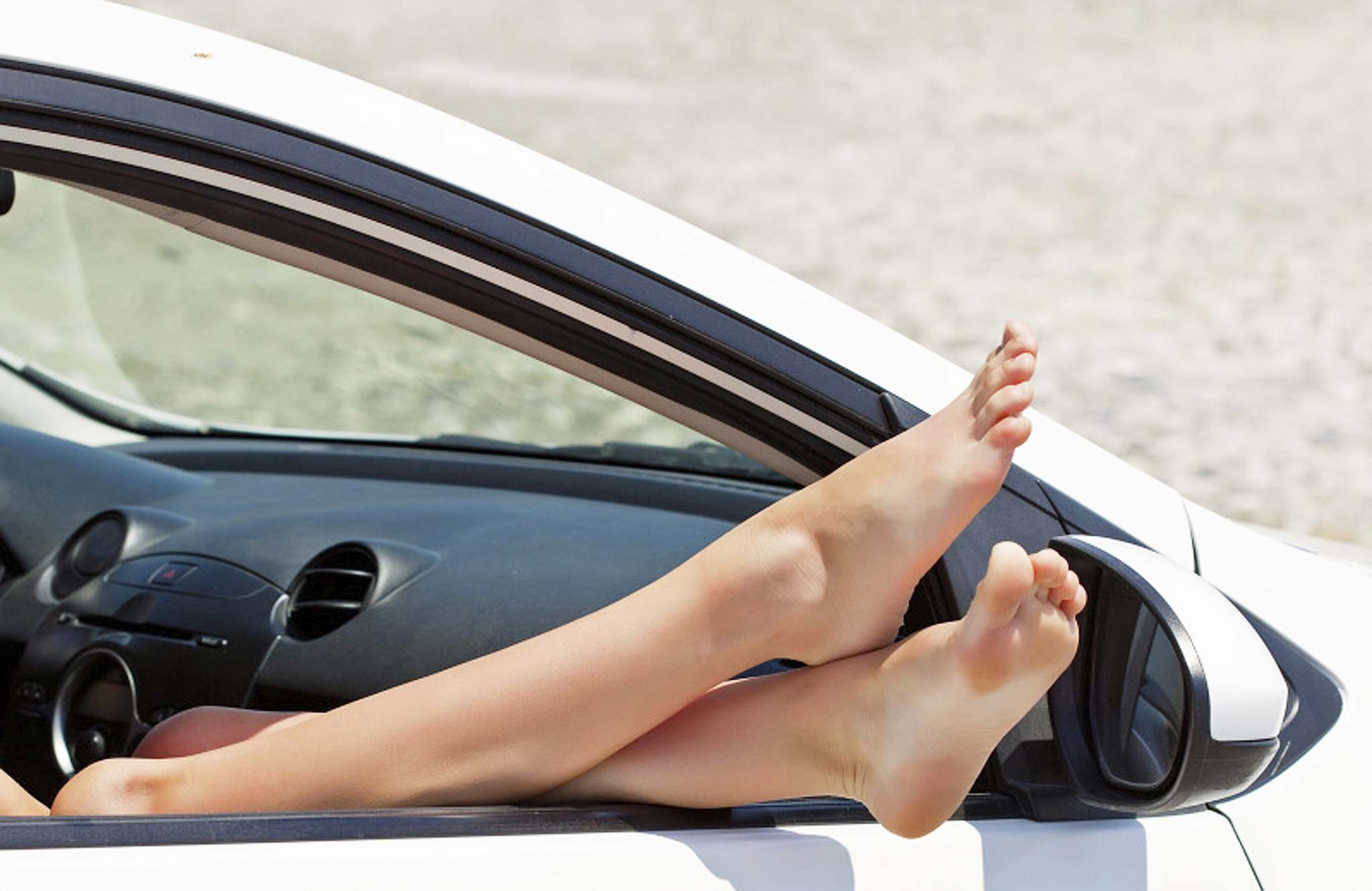 FotoliaPutting your feet up on or near the dash in a moving car is like playing Russian roulette with a fully loaded gun.