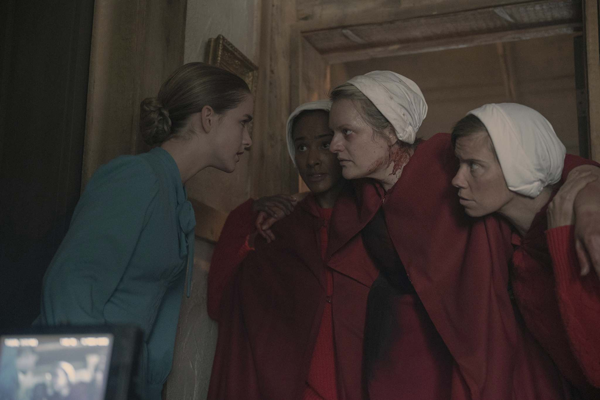 McKenna Grace, in blue, and Elisabeth Moss, centre right, in season four of The Handmaid's Tale.