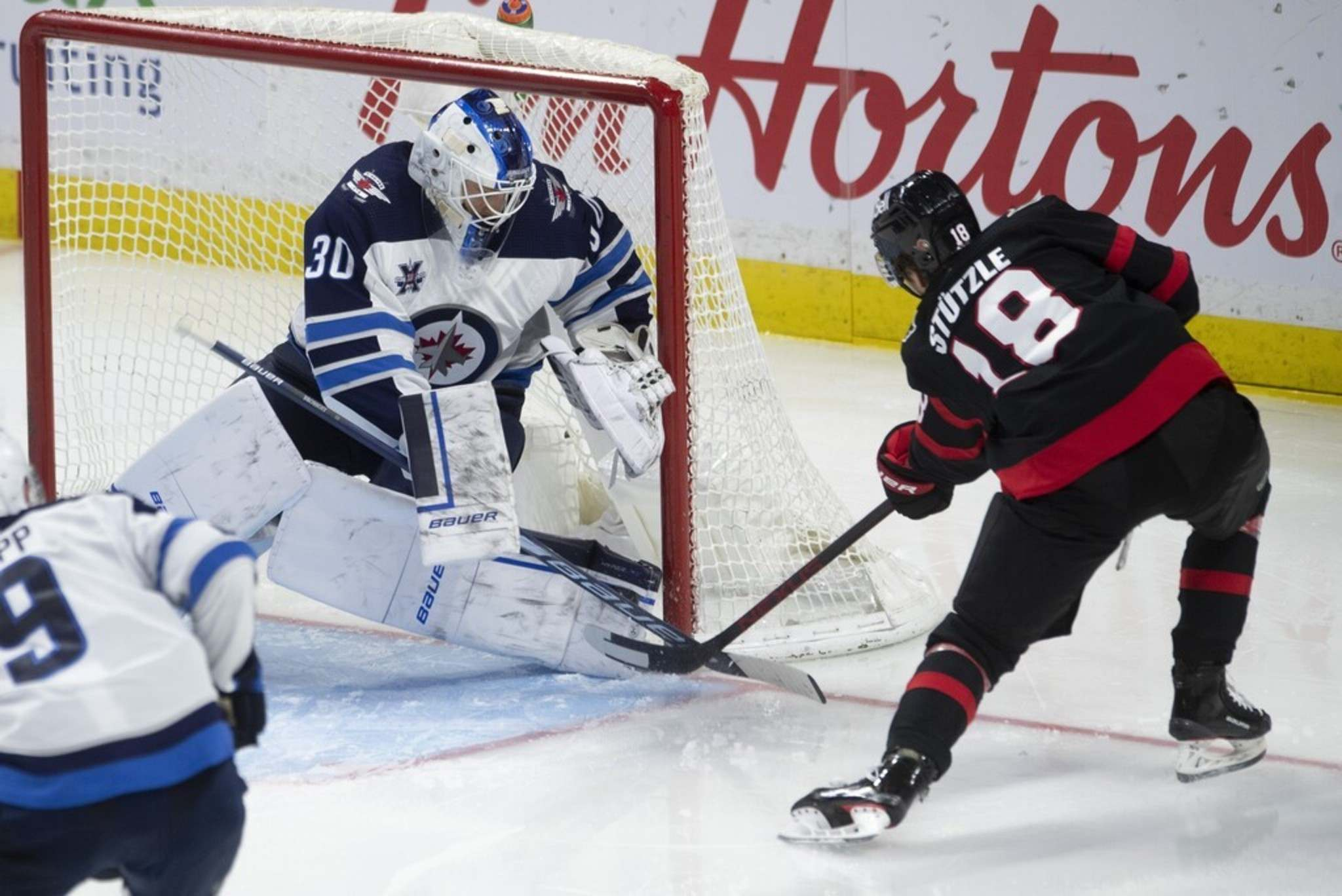 Winnipeg Jets goaltender Laurent Brossoit makes a pad save on Ottawa Senators left wing Tim Stützle during the third period in Ottawa, Monday. THE CANADIAN PRESS/Adrian Wyld</p>