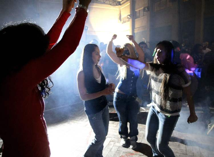 Soldiers and service members with the NATO led International Security Assistance Force dance as they celebrate the New Year eve at the NATO's headquarters in Kabul, Afghanistan Monday. (The Associated Press)