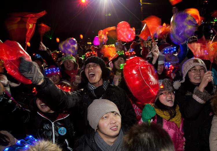 Chinese revellers wave national flags as they celebrate the New Year during a countdown at the Summer Palace in Beijing. (Andy Wong / The Associated Press)