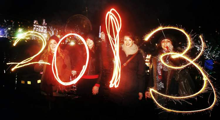 Katy Saunders, left, Alex Mueller, center left, Rebekka Frank and Arina Motamedi, right, play with sparklers ahead of welcoming in the new year during the 2013 Edinburgh Hogmanay celebrations Monday. (CP)