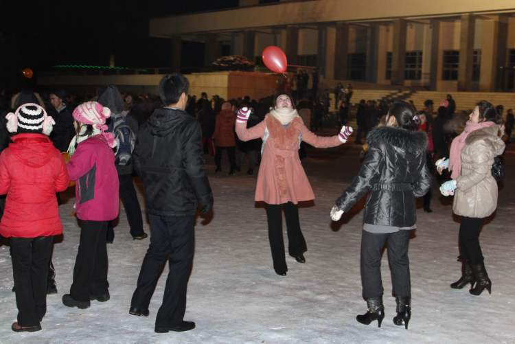 "North Koreans play with a balloon as they wait outside Pyongyang stadium for the countdown to the new year in Pyongyang, North Korea. North Koreans celebrated the arrival of the new year, marked as ""Juche 102"" on North Korean calendars. ""Juche"" means ""self reliance,"" the North Korean ideology of independence promoted by North Korean founder Kim Il Sung, and modern-day North Korean calendars start with the year of his birth in 1912.  (The Associated Press)"