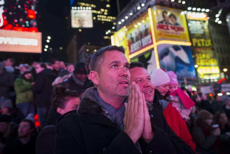 Cean Orrett, 45, centre, and Gareth Edmondson-Jones, 46, of San Diago, both recently married in New York, react to positive predictions for President Barack Obama as crowds watch election results in Times Square, Tuesday, in New York. After a year of campaigning, polls have begun to close after Americans across the United States headed to the polls to decide the winner of the tight presidential race between President Barack Obama and Republican presidential candidate, former Massachusetts Gov. Mitt Romney.  (John Minchillo / The Associated Press)