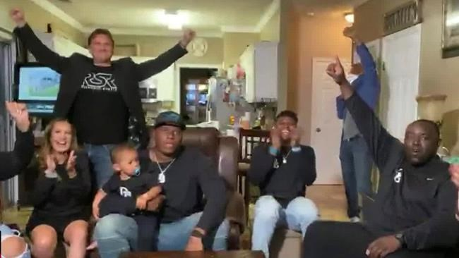 In this still image from video provided by the NFL, Derrick Brown, wearing cap, watches during the NFL football draft Thursday, April 23, 2020, as people with him applaud. (NFL via AP)