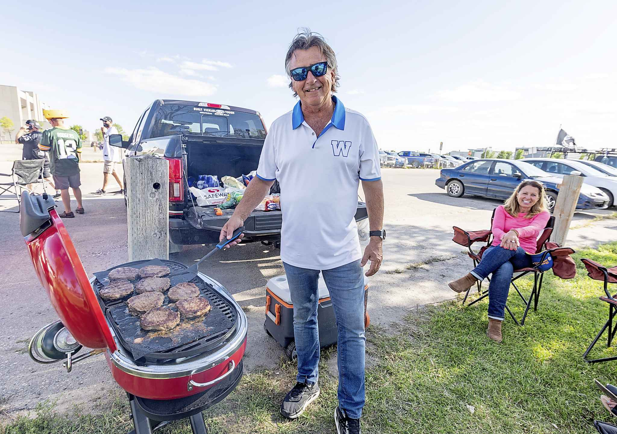 Tailgater David Olivier grilles up some burgers in a parking lot for his family before the NFL pre-season game between the Green Bay Packers and Oakland Raiders at IG Field Thursday evening.