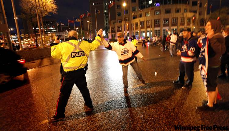 A Winnipeg Jets fan high-fives a city police officer directing traffic at Portage and Main Tuesday evening as the crowd emptied out of The Forks and gathered at the city's famous intersection.