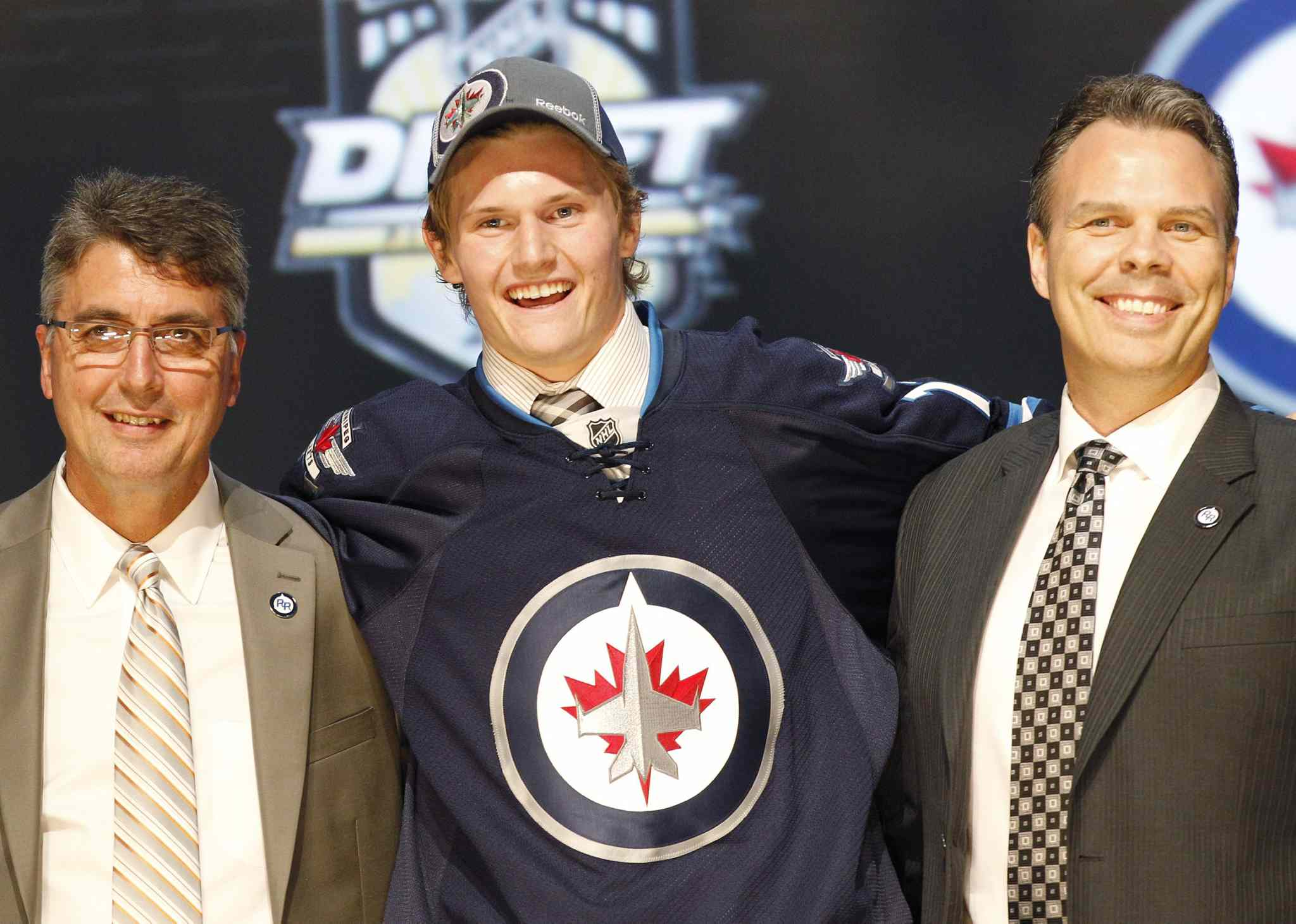 Jacob Trouba, center, a defenseman, stands with officials from the Winnipeg Jets after being chosen ninth overall in the first round of the NHL hockey draft on Friday, June 22, 2012, in Pittsburgh. (AP Photo/Keith Srakocic)