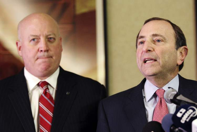 NHL Commissioner Gary Bettman, right, and deputy commissioner Bill Daly speak to reporters in New York. The NHL is pushing for a 50 game schedule to start Jan 15