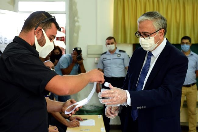 In this photo taken on Sunday, Oct. 11, 2020, Turkish Cypriot leader and candidate Mustafa Akinci casts his ballot at a polling station during the Turkish Cypriots election for a new leader in the Turkish occupied area in the north part of the divided capital Nicosia, Cyprus, Sunday, Oct. 11, 2020. Turkish Cypriots vote on Sunday Oct. 18, 2020 in a leadership runoff that could decide if they want to retain more control over their own affairs or steer even closer to an increasingly domineering Turkey. (AP Photo/Nedim Enginsoy)