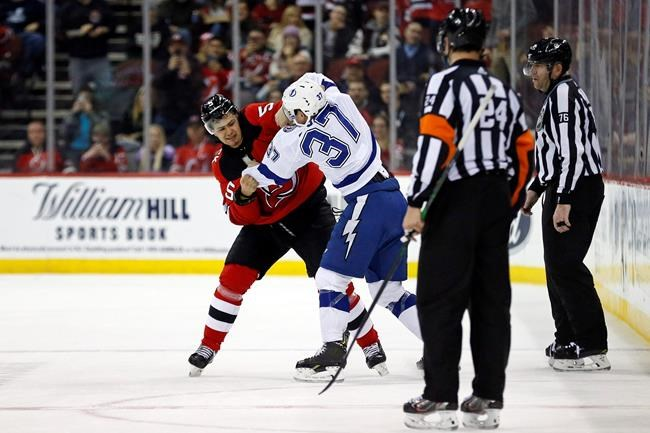 Tampa Bay Lightning center Yanni Gourde (37) fights with New Jersey Devils defenseman Connor Carrick during the second period of an NHL hockey game Sunday, Jan. 12, 2020, in Newark, N.J. (AP Photo/Adam Hunger)