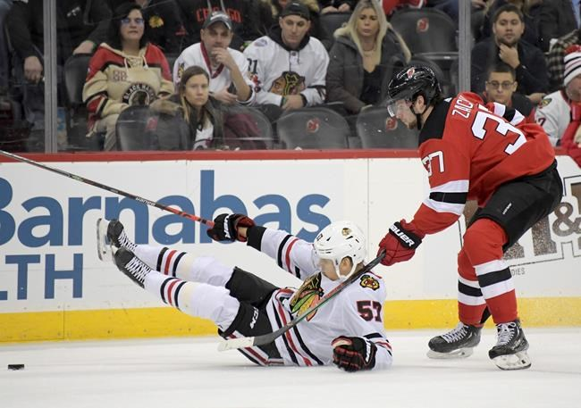 Chicago Blackhawks left wing Anton Wedin (57) hits the ice as he chases after the puck with New Jersey Devils center Pavel Zacha (37) during the first period of an NHL hockey game Friday, Dec. 6, 2019, in Newark, N.J. (AP Photo/Bill Kostroun)