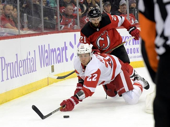 New Jersey Devils center Kyle Palmieri (21) cross checks Detroit Red Wings defenseman Patrik Nemeth (22) to the ice drawing a penalty during the second period of an NHL hockey game Saturday, Nov. 23, 2019, in Newark, N.J. (AP Photo/Bill Kostroun)