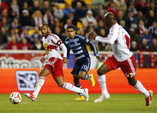 New York Red Bulls forward Thierry Henry (14) passes to forward Bradley Wright-Phillips (99) as Sporting Kansas City midfielder Jorge Claros (20) closes in during the second half in an MLS playoff soccer match at Red Bull Arena in Harrison, N.J., Thursday, Oct. 30, 2014. The Red Bulls defeated Kansas City 2-1. (AP Photo/Rich Schultz)