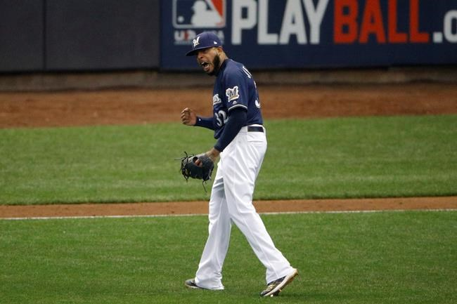 Milwaukee Brewers relief pitcher Jeremy Jeffress (32) reacts after a double play during the seventh inning of Game 2 of the National League Championship Series baseball game against the Los Angeles Dodgers Saturday, Oct. 13, 2018, in Milwaukee. (AP Photo/Charlie Riedel)