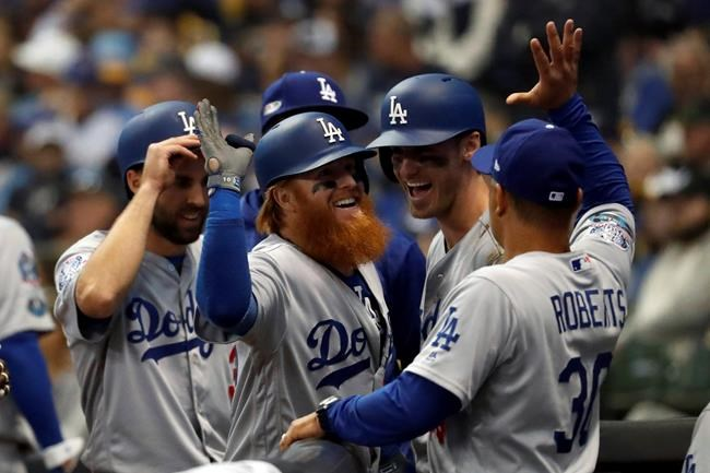 Los Angeles Dodgers' Justin Turner (10) celebrates with manager Dave Roberts (30) after hitting a two-run home run during the eighth inning of Game 2 of the National League Championship Series baseball game against the Milwaukee Brewers Saturday, Oct. 13, 2018, in Milwaukee. (AP Photo/Jeff Roberson)