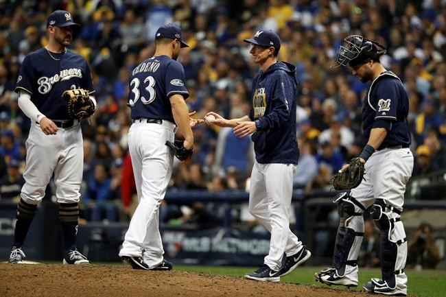 Milwaukee Brewers manager Craig Counsell removes relief pitcher Xavier Cedeno (33) during the ninth inning of Game 2 of the National League Championship Series baseball game against the Los Angeles Dodgers Saturday, Oct. 13, 2018, in Milwaukee. (AP Photo/Jeff Roberson)