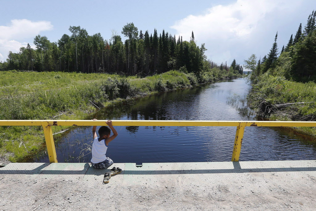 A boy from the Shoal Lake 40 First Nation sits on a bridge over a channel in a file photo.