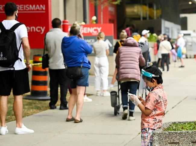A young boy plays on a phone as he waits in line at a COVID assessment centre at Mount Sinai Hospital during the COVID-19 pandemic in Toronto on Thursday, September 24, 2020. THE CANADIAN PRESS/Nathan Denette