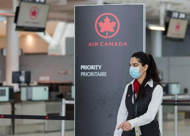An Air Canada employee works at Pearson International Airport in Toronto on Friday, March 20, 2020. THE CANADIAN PRESS/Nathan Denette