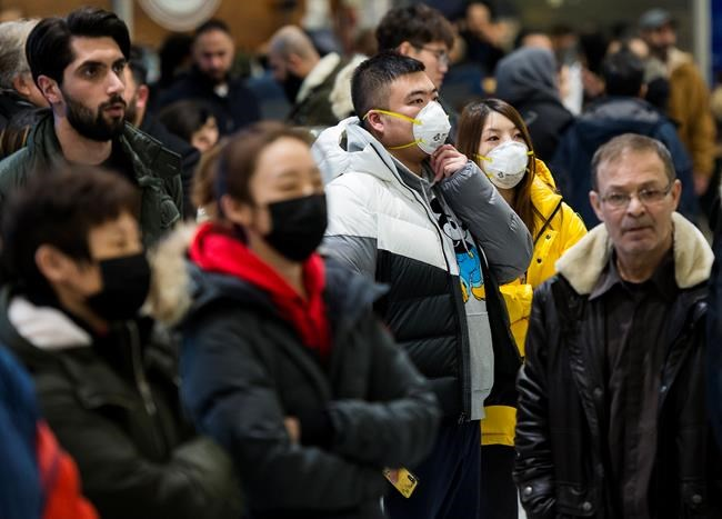 People wear masks as a precaution due to the coronavirus outbreak as they wait for the arrivals at the International terminal at Toronto Pearson International Airport in Toronto on Saturday, January 25, 2020. Canadian health officials announced a first presumed case in Ontario after the illness has sickened more than 1,200 people and killed at least 41 in China, the epicentre of the outbreak. THE CANADIAN PRESS/Nathan Denette