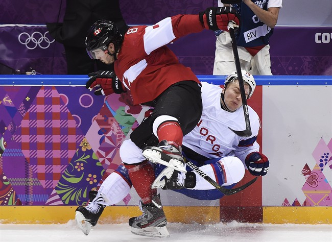 Canada defenceman Drew Doughty, left, hits Norway forward Per-Age Skroder, right, during second period period preliminary action at the 2014 Sochi Winter Olympics in Sochi, Russia on Thursday, February 13, 2014. THE CANADIAN PRESS/Nathan Denette