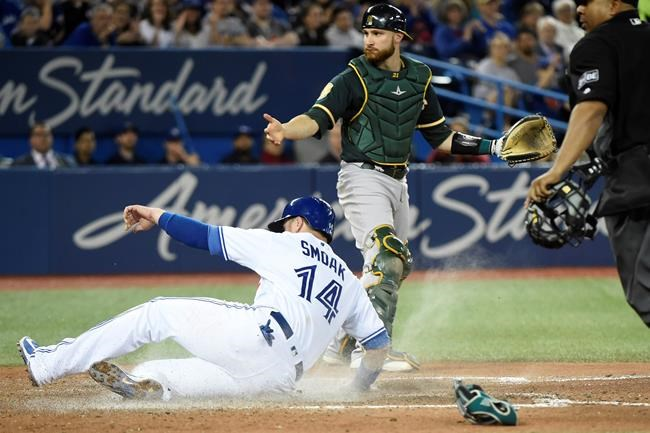 Toronto Blue Jays first baseman Justin Smoak (14) slides into home plate to score a run as Oakland Athletics catcher Jonathan Lucroy (21) looks on during fifth inning AL baseball action in Toronto on Thursday, May 17, 2018. THE CANADIAN PRESS/Nathan Denette