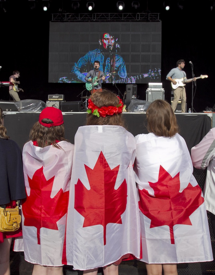 Three patriotic teens watch a performance by Toronto band The Elwins at Alderney Landing in Dartmouth, N.S., Monday. (Tim Krochak / The Canadian Press)