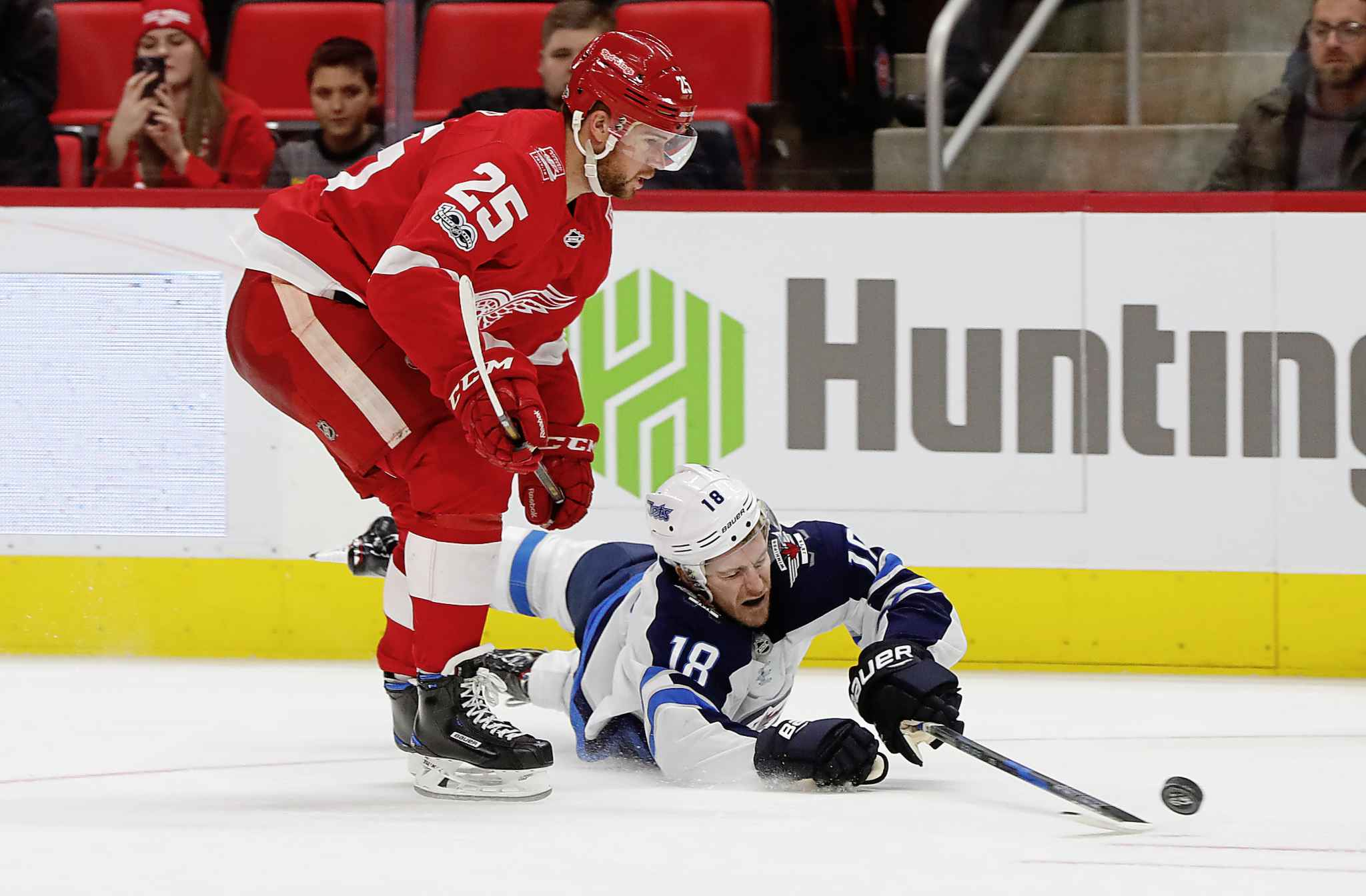Winnipeg Jets center Bryan Little tries to pass from the ice as Detroit Red Wings defenseman Mike Green defends in the third period of an NHL hockey game Tuesday in Detroit.
