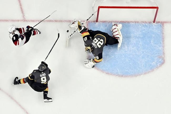 Arizona Coyotes center Clayton Keller, top left, shoots against Vegas Golden Knights goaltender Marc-Andre Fleury (29) and center Cody Glass during the second period of an NHL hockey game Saturday, Dec. 28, 2019, in Las Vegas. (AP Photo/David Becker)