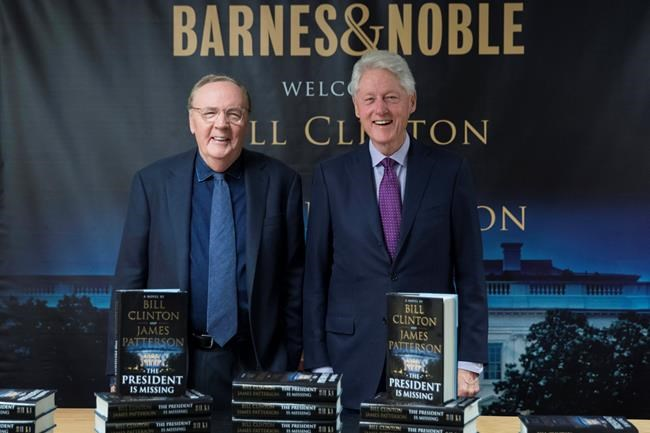 """FILE - In this June 5, 2018 file photo, former President Bill Clinton, right, and author James Patterson pose for photographers during an event to promote their new novel, """"The President is Missing,"""" in New York. Clinton's debut as a novelist is already one of the year's biggest hits. """"The President is Missing,"""" the thriller he co-wrote with James Patterson, sold 250,000 copies its first week. Alfred A. Knopf and Little, Brown and Co., the book's co-publishers, announced Wednesday, June 13 that the number includes hardcover, e-book and audio sales. (AP Photo/Mary Altaffer, File)"""