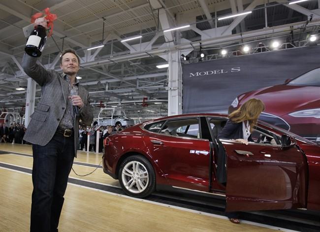 FILE - In this June 22, 2012 file photo, Tesla Motors Inc. CEO Elon Musk holds up a bottle of wine given as a gift from one of their first customers, right, during a rally at the Tesla factory in Fremont, Calif. When billionaire entrepreneur Elon Musk published fanciful plans to shoot capsules full of people at the speed of sound through a tube connecting Los Angeles and San Francisco, he asked the public to perfect his rough plans. From tinkerers to engineers, the race is on. (AP Photo/Paul Sakuma, File)