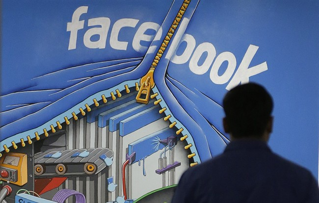 FILE - In this Friday, March 15, 2013 file photo, a Facebook employee walks past a sign at Facebook headquarters in Menlo Park, Calif. Facebook on Friday, June 21, 2013 said a bug in its system caused 6 million users' contact information to be inadvertently exposed. (AP Photo/Jeff Chiu, File)