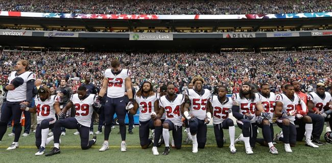 FILE - In this Oct. 29, 2017, file photo, Houston Texans players kneel and stand during the singing of the national anthem before an NFL football game against the Seattle Seahawks, in Seattle. The NFL Players Association filed a grievance with the league challenging its national anthem policy. The union says that the new policy, which the league imposed without consultation with the NFLPA, is inconsistent with the collective bargaining agreement and infringes on player rights. (AP Photo/Elaine Thompson, File)