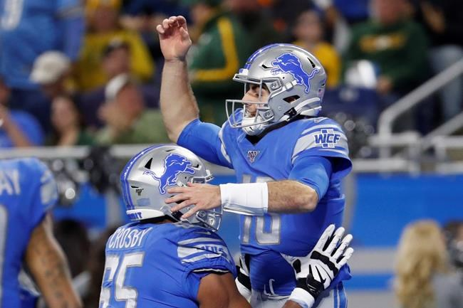 FILE - In this Dec. 29, 2019, file photo, Detroit Lions quarterback David Blough is lifted by teammate offensive tackle Tyrell Crosby (65) after scoring on a 19-yard reception during the first half of an NFL football game against the Green Bay Packers, in Detroit. Tom Brady tried it. Nick Foles perfected it. More quarterbacks are doing it. Catching passes isn't just for wide receivers, tight ends and running backs anymore. (AP Photo/Rick Osentoski, File)
