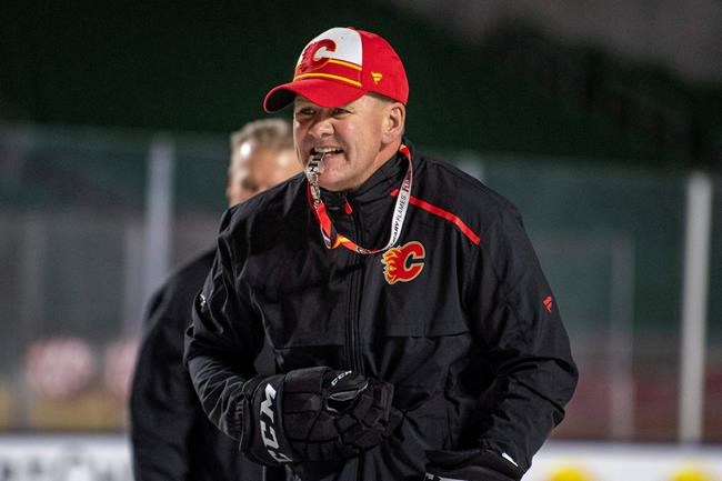 """FILE - In this Oct. 25, 2019, file photo, Calgary Flames coach Bill Peters watches practice in Regina, Saskatchewan, ahead of the NHL Heritage Classic outdoor hockey game against the Winnipeg Jets. Calgary Flames general manager Brad Treliving said the team is looking into an accusation that head coach Bill Peters directed racial slurs toward a Nigerian-born hockey player a decade ago in the minor leagues, then arranged for the player's demotion when he complained. Akim Aliu tweeted Monday, Nov. 25, 2019, that Peters """"dropped the N bomb several times towards me in the dressing room in my rookie year because he didn't like my choice of music."""" (Liam Richards/The Canadian Press via AP, File)"""