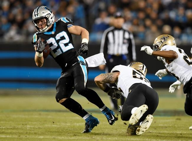FILE - In this Dec. 17, 2018, file photo, Carolina Panthers' Christian McCaffrey (22) evades a tackle by New Orleans Saints' A.J. Klein (53) during the first half of an NFL football game in Charlotte, N.C. McCaffrey would truly impress if he can have a huge game against two-time Defensive Player of the Year Aaron Donald and the Los Angeles Rams' solid defense this week. (AP Photo/Mike McCarn, File)
