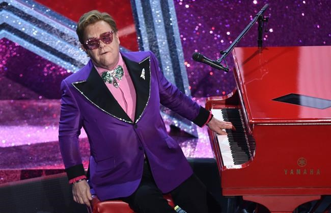 """FILE - In a Sunday, Feb. 9, 2020 file photo, Elton John performs """"(I'm Gonna) Love Me Again"""" nominated for the award for best original song from """"Rocketman"""" at the Oscars, at the Dolby Theatre in Los Angeles. Elton John and the Foo Fighters announced cancellations Monday, March 16, for upcoming performances, joining other artists like The Who, Blake Shelton and Dan + Shay. (AP Photo/Chris Pizzello, File)"""