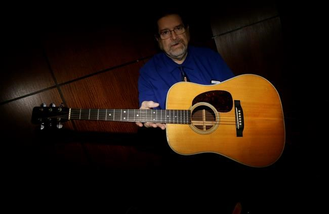 FILE - In this Friday, Oct. 13, 2017, file photo, Garry Shrum, a music memorabilia specialist at Heritage Auctions, displays an acoustic guitar that belonged to Bob Dylan in Dallas. The 1963 Martin D-28 acoustic guitar played by Dylan at notable concerts in 1970s sold Saturday, Nov. 11, at an auction for nearly $400,000. (AP Photo/LM Otero, File)