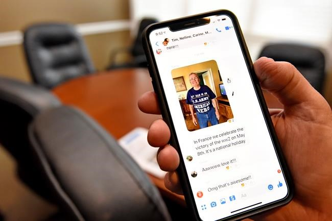 "In this May 8, 2019, photo, Allen Henderson shows a photo of his half-brother Andre Gantois wearing a T-shirt that says ""My Dad is a U.S. Army American Hero"" on his cell phone. Both Andre and Allen acknowledge how lucky they are not only to have found each other thanks to a DNA test but also that Wilburn Henderson survived Normandy and its aftermath to father them. (AP Photo/Richard Shiro)"