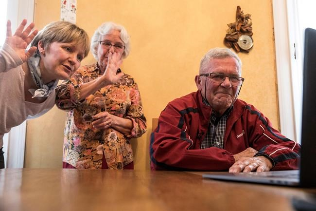 "In this photo taken May 8, 2019, Andre Gantois, his wife Rosine, center, and daughter Isabelle talk to his half-brother Allen Henderson, of the U.S, during a video-conference call in Ludres, eastern France. Andre Gantois figured he'd likely go to his grave without ever knowing who his father was until a DNA test connected him with his half-brother. Having married and with plans to start a family of his own, Gantois felt compelled to put a name and a face to the patchy story and to fill what his wife now says was ""a huge hole"" in his life. (AP Photo/Jean-Francois Badias)"