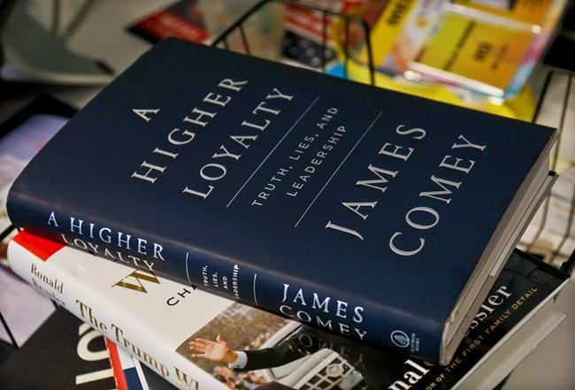 "A copy of former FBI Director James Comey's new book, ""A Higher Loyalty: Truth, Lies and Leadership,"" is on display, Friday, April 13, 2018, in New York. In the book, Comey compares U.S. President Donald Trump to a mob boss demanding loyalty, suggests he's unfit to lead and mocks the president's appearance. (AP Photo/Bebeto Matthews)"