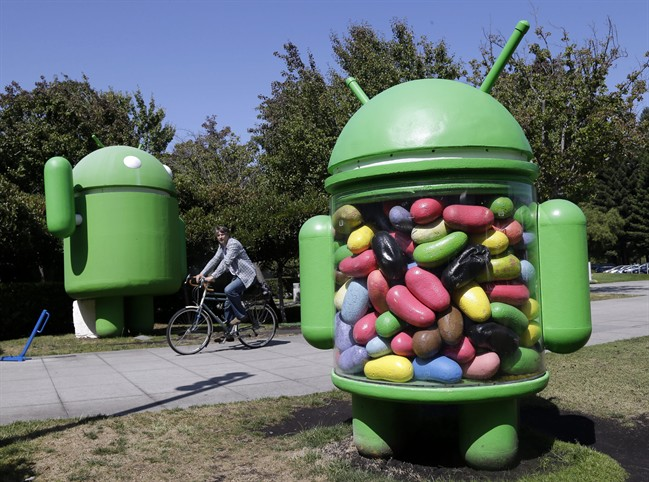 In this June 5, 2014 photo, a man rides a bike through the Google campus in Mountain View, Calif. Google reports quarterly financial results on Thursday, July 17, 2014. (AP Photo/Marcio Jose Sanchez)