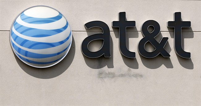 This Wednesday, May 14, 2014 photo shows the company logo at an AT&T store in Dedham, Mass. AT&T reports quarterly financial results on Wednesday, July 23, 2014. (AP Photo/Steven Senne)