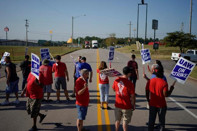 FILE - In this Sept. 16, 2019, file photo striking plant workers block the passage of two trucks outside the General Motor assembly plant in Bowling Green, Ky. A tentative four year contract with striking General Motors gives workers a mix of pay raises, lump sum payments and an $11,000 signing bonus. (AP Photo/Bryan Woolston, File)