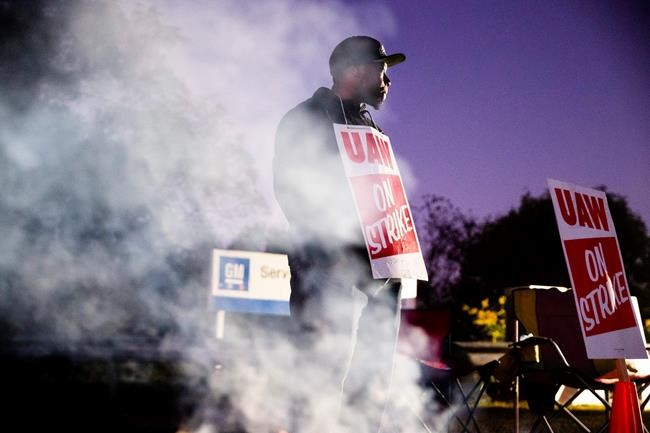 FILE- In this Sept. 27, 2019, file photo worker Omar Glover pickets outside a General Motors facility in Langhorne, Pa. A tentative four year contract with striking General Motors gives workers a mix of pay raises, lump sum payments and an $11,000 signing bonus. (AP Photo/Matt Rourke, File)